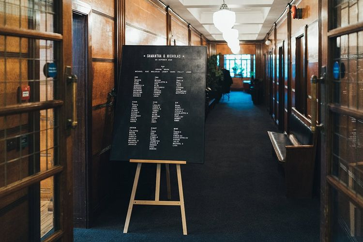 Black and white peg board seating plan at Town Hall wedding in East London with black bridesmaid dresses