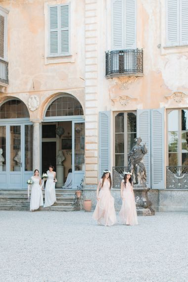 Bridesmaids in Peach Dresses and Flower Crowns Walking Along the Courtyard