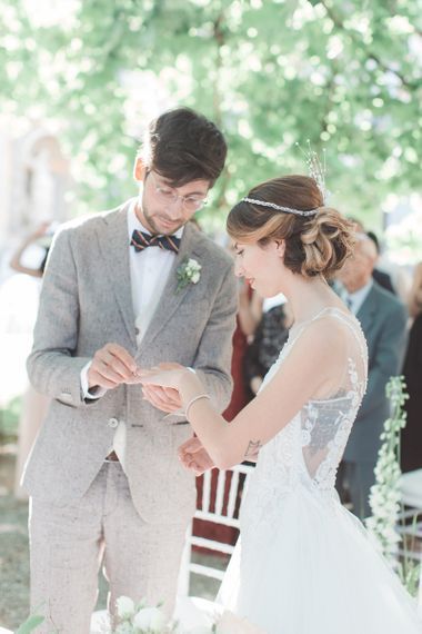 Bride in Lace Atelier Eme Wedding Dress and Headdress Exchanging Vows with Her Groom in Beige Suit and Bow Tie