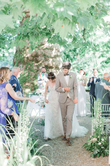 Bride in Lace Atelier Eme Wedding Dress and Groom in Beige Suit Walking Up the Aisle as Husband and Wife