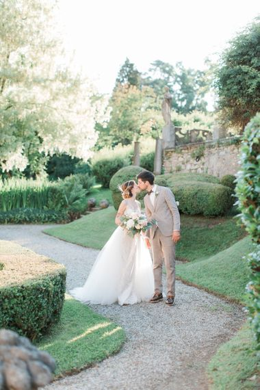 Bride in Lace Atelier Eme Wedding Dress and Groom in Beige Wedding Suit
