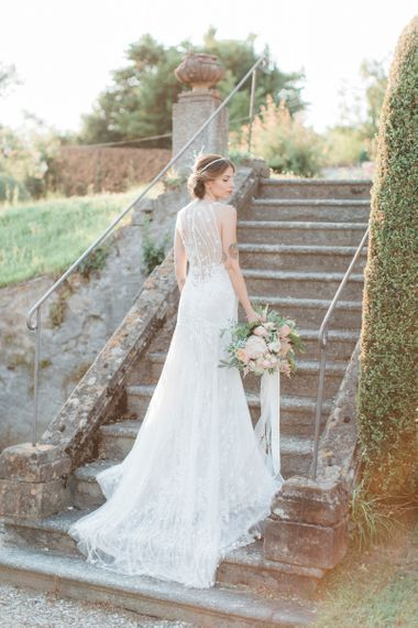 Bride in Lace Atelier Eme Wedding Dress with Ornate Headdress and Romantic Bouquet