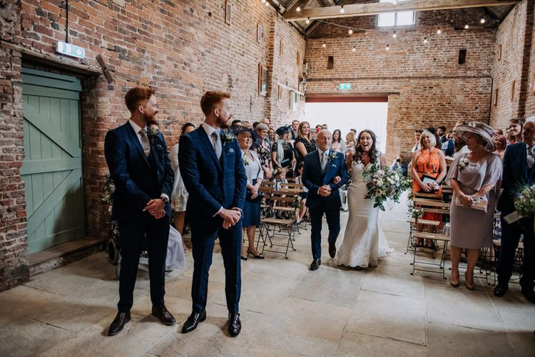 Wedding Ceremony Bridal Entrance in Lace Roland Joyce Bridal Wedding Dress and Groom in Navy Suit