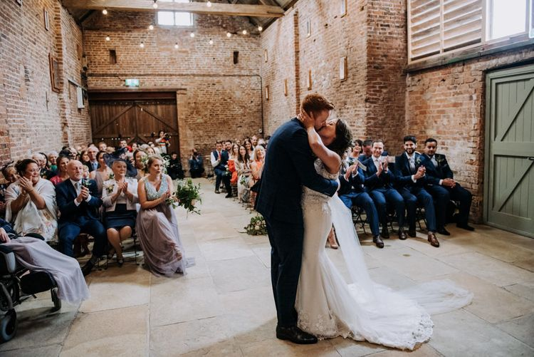 Bride in Lace Roland Joyce Bridal Wedding Dress and Groom in Navy Suit Embracing During Wedding Ceremony