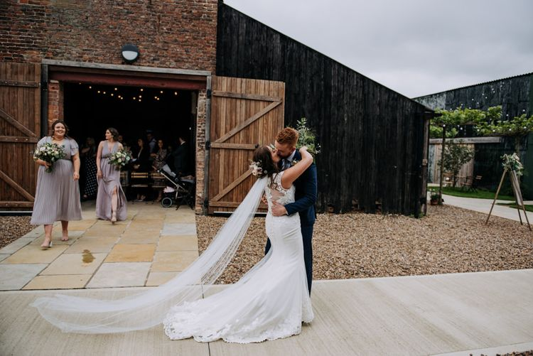 Bride in Lace Roland Joyce Bridal Wedding Dress and Groom in Navy Suit Kissing Outside Barn Wedding Venue