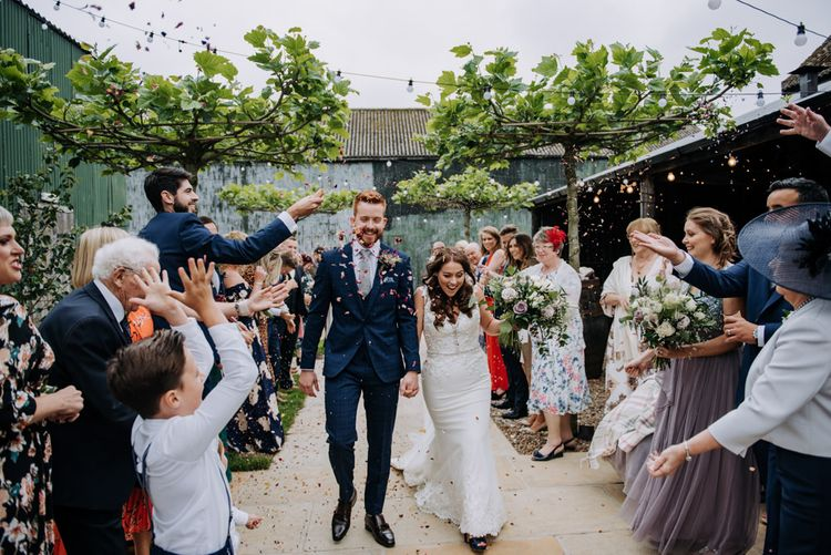 Confetti Moment with Bride in Lace Roland Joyce Bridal Wedding Dress and Groom in Navy Suit