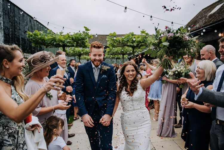 Confetti Exit with Bride in Lace Roland Joyce Bridal Wedding Dress and Groom in Navy Suit