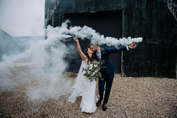 Bride in Roland Joyce Wedding Dress and Groom in Navy Suit Holding White Smoke Bombs