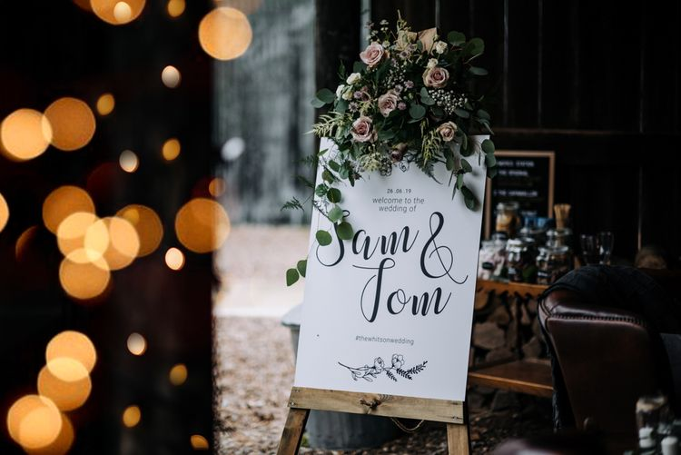Calligraphy Wedding Welcome Sign with Floral Decor on a Wooden Easel