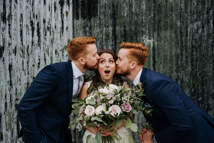 Bride Being Kissed on Cheeks by Twin Brothers
