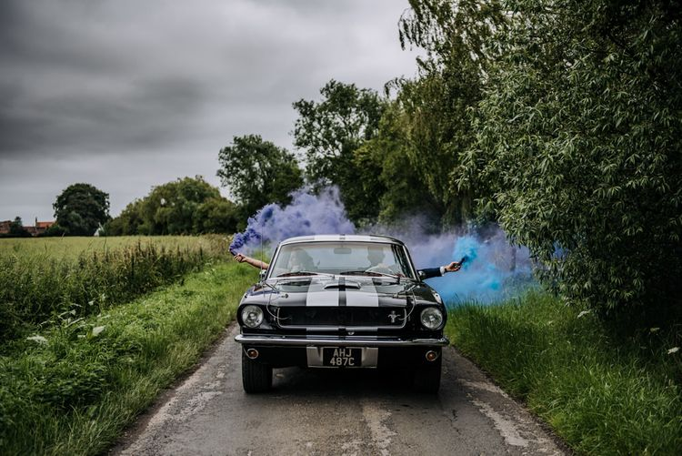 Bride and Groom Driving Ford Mustang Wedding Car Holding Smoke Bombs Out the Side
