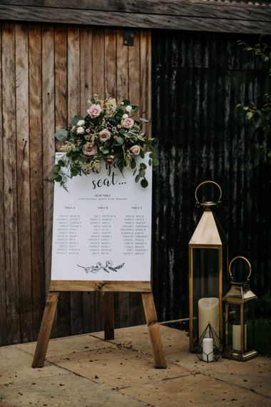 Calligraphy Seating Chart on Wooden Easel Decorated with Pink Flowers