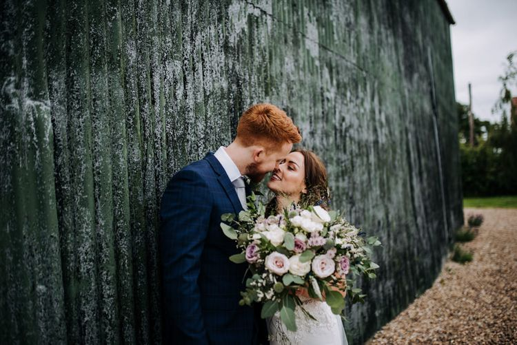 Bride in Lace Roland Joyce Bridal Wedding Dress Holding a Pink Rose Bouquet Kissing Her  Groom in a Navy Suit