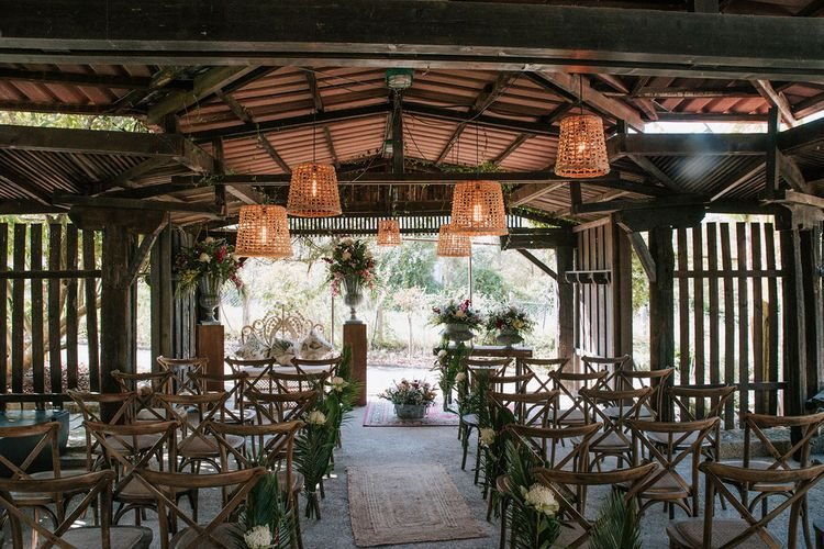 wooden 'pagoda' wedding ceremony with wicker lamps and botanical plant decor