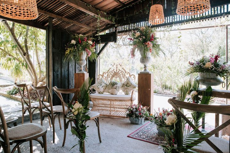 wooden 'pagoda' wedding ceremony with wicker lamps and chairs and botanical plant decor