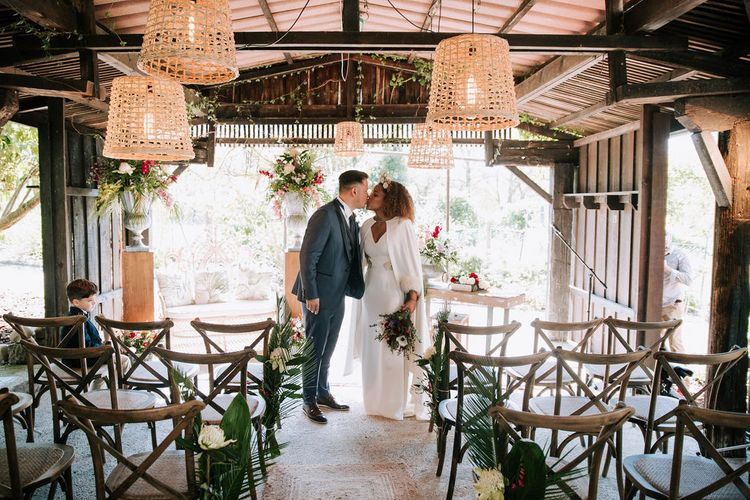 Bride with Afro Hair in Gold Headdress, Patricia Meléndez Wedding Dress and coat and Groom in Navy Suit Kissing in wooden 'pagoda' decorated with wicker lamps and botanical plants