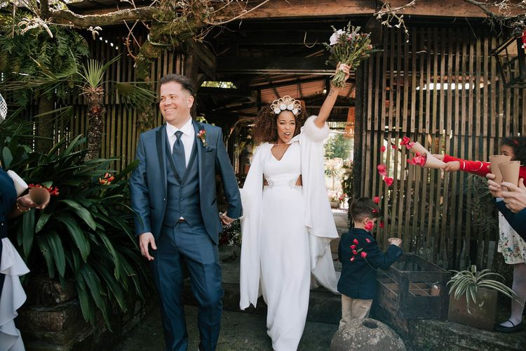 Bride with Afro Hair in Gold Headdress, Patricia Meléndez Wedding Dress and coat and Groom in Navy Suit Walking Out The Wedding Ceremony