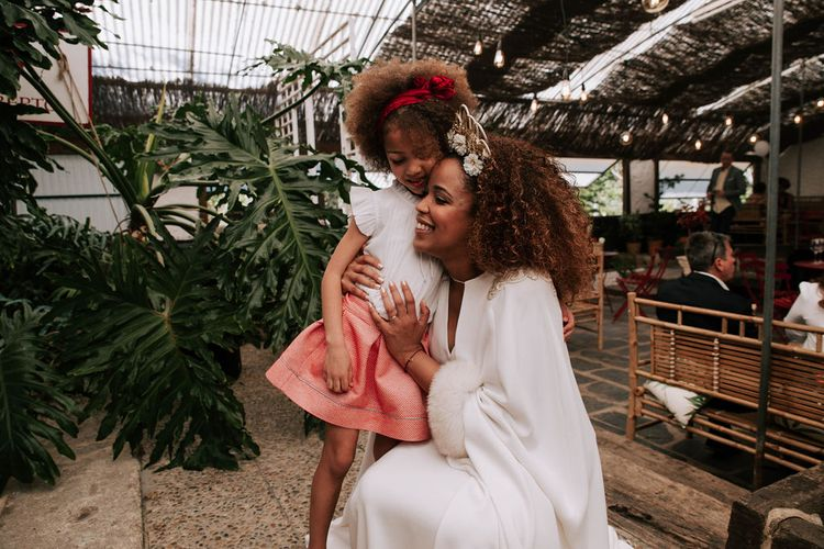 Bride with Afro Hair in Gold Headdress, Patricia Meléndez Wedding Dress and coat Hugging Little Girl