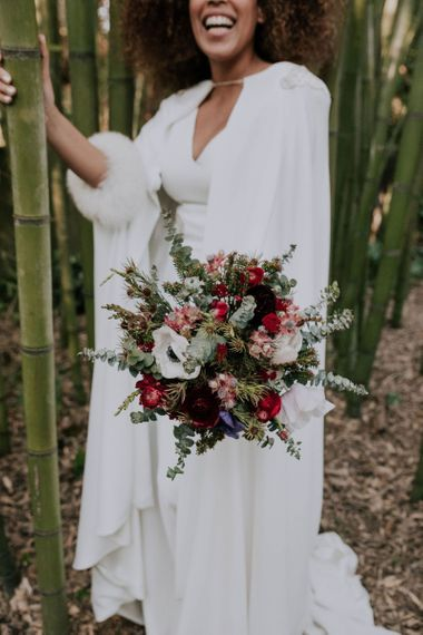 Bride in Patricia Meléndez Wedding Dress and Coat with blue fox wristband Holding Green, Red and White Bouquet