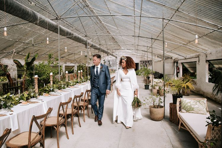 Bride with Afro Hair in Gold Headdress, Patricia Meléndez Wedding Dress and coat and Groom in Navy Suit Walking Through Glasshouse Wedding Venue