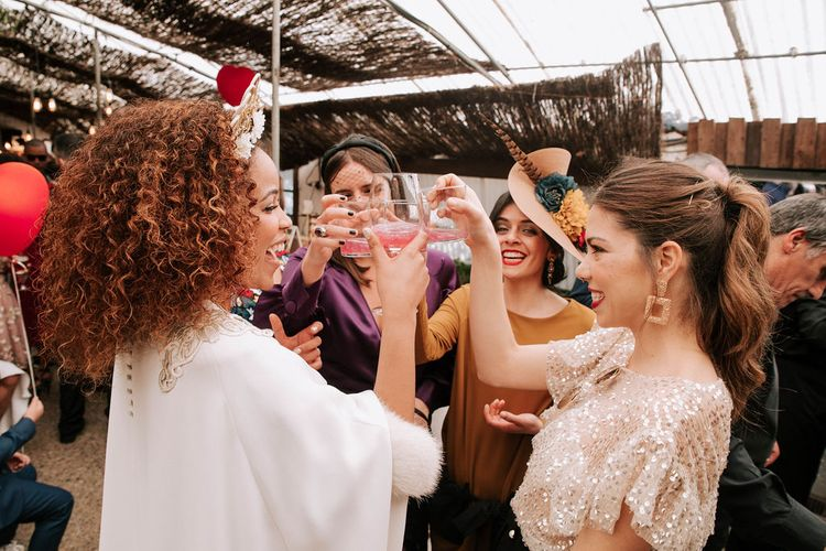 Bride with Afro Hair in Gold Headdress, Patricia Meléndez Wedding Dress and coat Enjoying a Drink with her friends