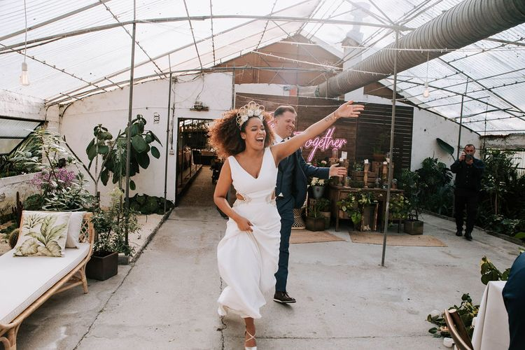 Bride with Afro Hair in Gold Headdress and Patricia Meléndez Wedding Dress and Groom in Navy Suit Enterting Glasshouse Wedding Venue