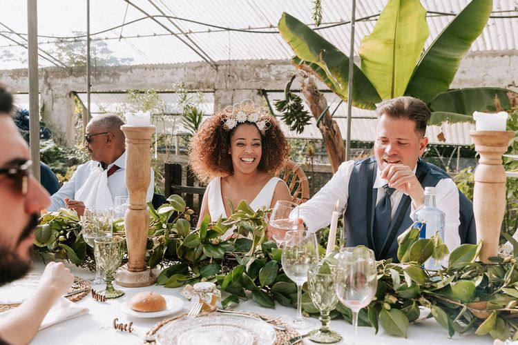 Bride with Afro Hair in Gold Headdress and Patricia Meléndez Wedding Dress and Groom in Navy Suit Enjoying Botanical Wedding Reception