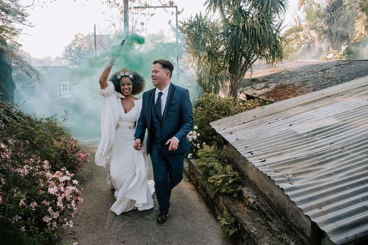 Bride with Afro Hair in Gold Headdress, Patricia Meléndez Wedding Dress and coat and Groom in Navy Suit Waving Coloured Flares