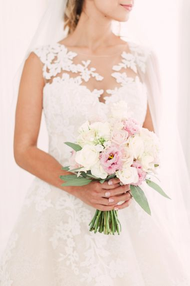 Bride in Lace Illusion Neck Wedding Dress Holding Her Pink and White Rose Bouquet