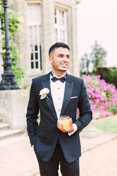 Stylish Groom in a Black Tie Suit with Bow Tie and White Flower Buttonhole