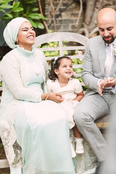 Flower Girl and Her Parents Laughing on a Bench