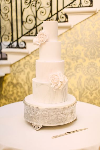 Elegant White Wedding Cake with Marble Bottom Tier and Rose Decor