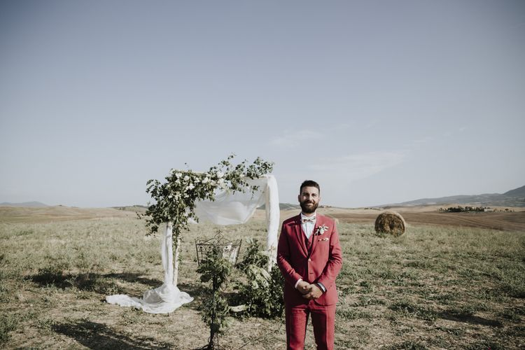 Groom in red suit waits at altar for bride