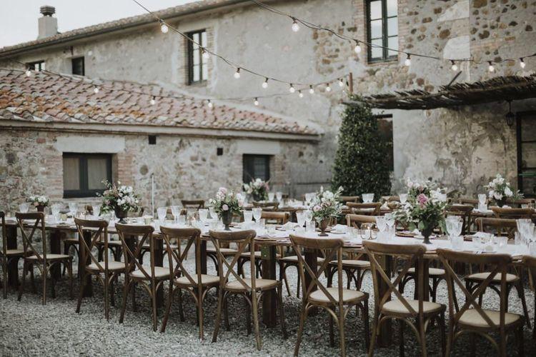 Outdoor wedding breakfast with festoon lighting