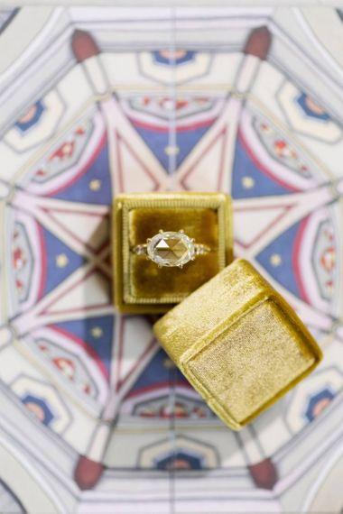 Diamond Engagement Ring in Yellow Wedding Box Resting on Celestial Wedding Invitation
