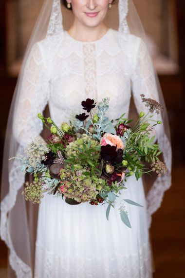 Bride in Lace Lihi Hod Sophia Wedding Dress Holding a Green and Red Winter Wedding Bouquet