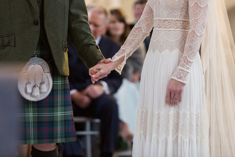 Wedding Ceremony with Bride in Delicate Lace Lihi Hod Sophia Wedding Dress with Long Sleeves and Groom in Traditional Tartan Kilt Holding Hands at the Altar