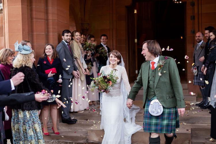 Confetti Moment with Bride in Delicate Lace Lihi Hod Sophia Wedding Dress with Long Sleeves and Groom in Traditional Tartan Kilt