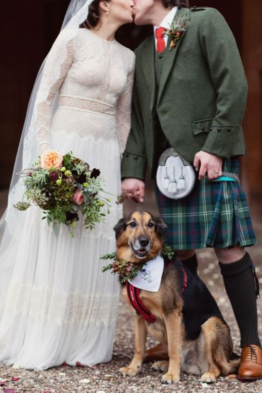 Bride in Delicate Lace Lihi Hod Sophia Wedding Dress with Long Sleeves and Groom in Traditional Tartan Kilt Posing with Pet Dog