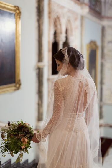 Bride in Delicate Lace Lihi Hod Sophia Wedding Dress with Long Sleeves Standing in the Grand Hall of Mount Stuart in Scotland