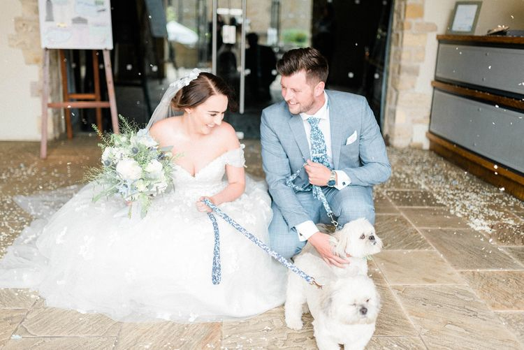 Bride in Appliqué Ian Stuart Wedding Dress and Groom in Most Suitable Blue Check Wedding Suit with Their Pet Dogs