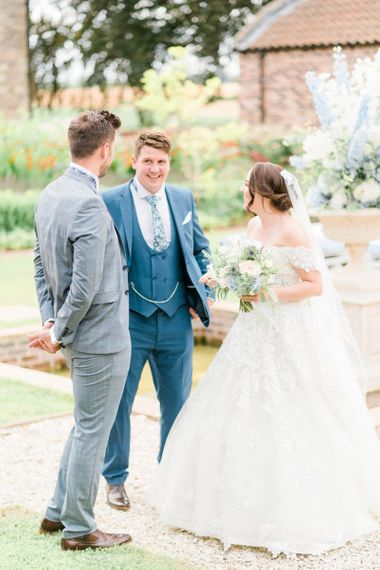 Bride in Appliqué Ian Stuart Wedding Dress and Groom in Most Suitable Blue Check Wedding Suit Talking to Wedding Guests