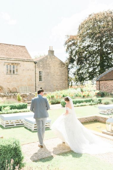Beautiful Bride in Appliqué Ian Stuart Wedding Dress and Groom in Blue Check Suit Walking Through The Gardens at The Priory Barns and Cottages