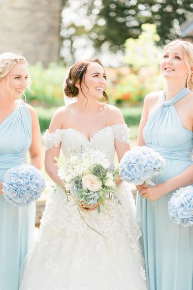 Bride in Appliqué Ian Stuart Wedding Dress and Bridesmaids in Blue Multiway Dresses with Blue Hydrangea Bouquets