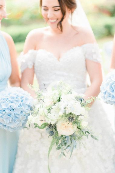 Bride in Appliqué Ian Stuart Wedding Dress  with Bardot Neckline and White and Blue Wedding Bouquet