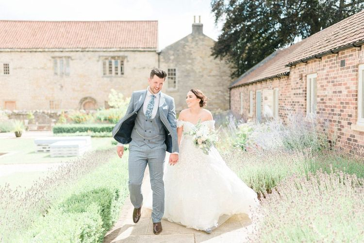 Bride in Appliqué Ian Stuart Wedding Dress and Groom in Most Suitable Blue Check Wedding Suit Walking Through The Gardens