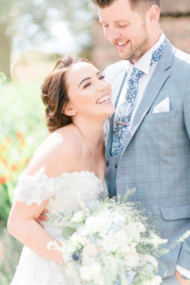 Bride in Appliqué Ian Stuart Wedding Dress and Groom in Most Suitable Blue Check Wedding Suit Laughing