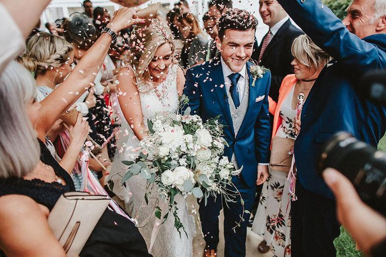 Confetti Moment | Bride in Lace Mikaella Bridal Gown | Groom in Navy Remus Uomo Suit & Grey Waistcoat | Blush, Rustic Luxe Wedding at Ever After, Dartmoor | Dan Ward Photography | CupcakeVideos