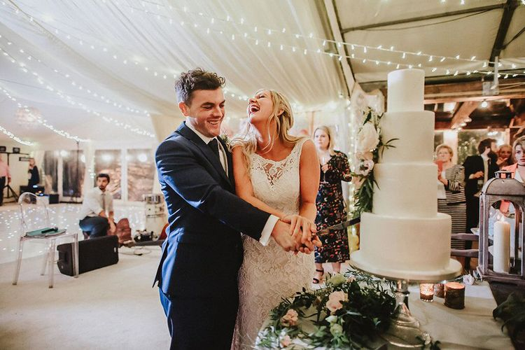 Cutting the Cake | Bride in Lace Mikaella Bridal Gown | Groom in Navy Remus Uomo Suit & Grey Waistcoat | Blush, Rustic Luxe Wedding at Ever After, Dartmoor | Dan Ward Photography | CupcakeVideos