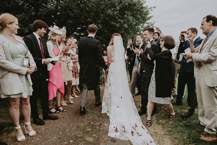 Confetti Exit | Bride in Lace Rime Arodaky Wedding Dress | Groom in Henry Herbert Tailors Suit | English Country Garden Marquee Wedding at the Family Home on the Isle of Wight | Jason Mark Harris Photography